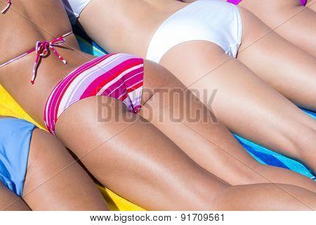 Girls in bikini sunbathing at the beach