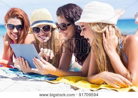 Happy friends wearing sun glasses and using tablet at the beach