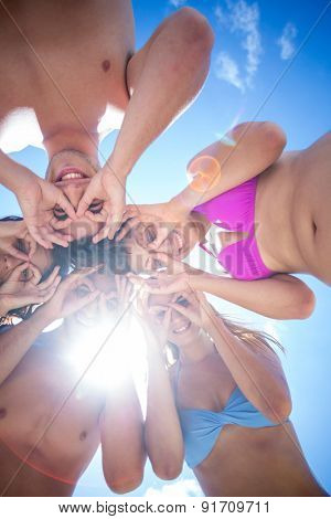 Happy friends standing in circle doing funny face at the beach