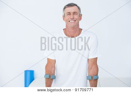 Patient standing with crutch looking at camera in medical office