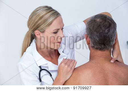 Doctor examining her patient shoulder in medical office