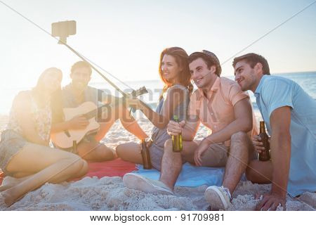 Happy hipsters taking pictures with selfie stick at the beach
