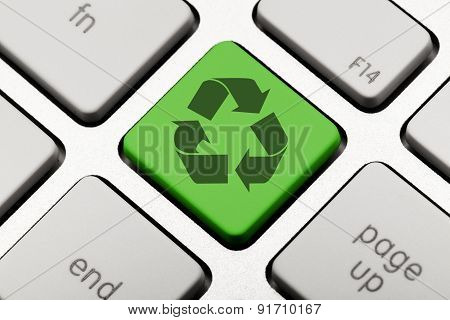 Green recycling symbol on a computer keyboard