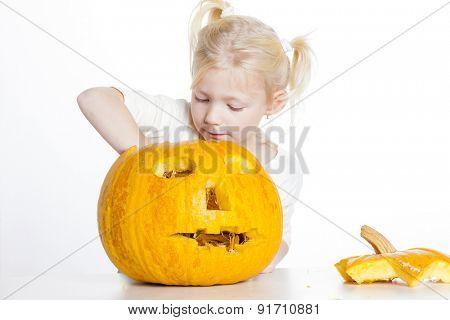 little girl carving pumpkin for Halloween