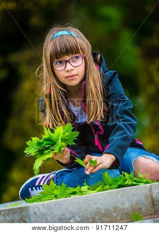 Little girl playing the green maple leaf. In the hands of a bunch of green maple leaf.