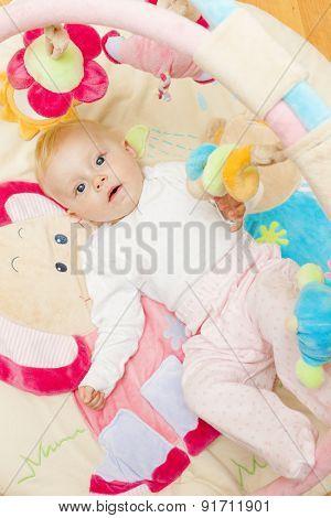 baby girl lying on playing mat