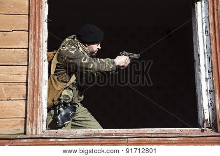 The Millitary Man With Black Gun In His Hands Is Aiming To Shoot