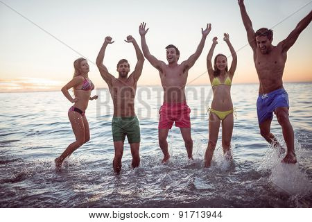 Happy friends having fun in the water at the beach