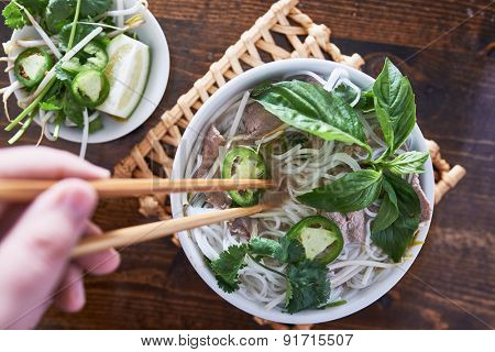 vietnamese pho with beef being eaten with chopsticks
