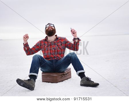 lost hipster on the salt flats sitting on suit case finds what he is looking for