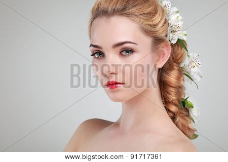 Beautiful girl, isolated on a light - grey background with varicoloured flowers in hairs, emotions, cosmetics