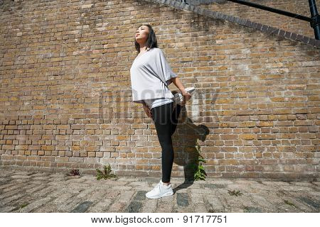 Full length of young fit woman stretching against brick wall