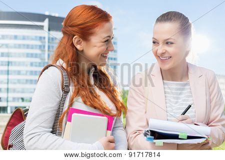 Happy young female college students studying outdoors