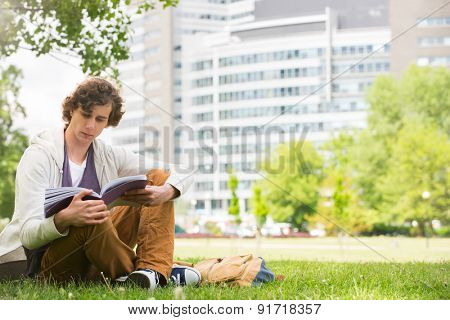 Full length of young man reading book on college campus