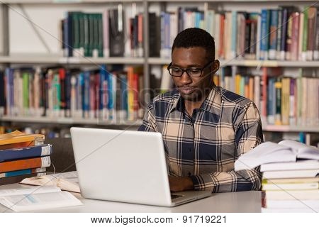 Happy African Male Student With Laptop In Library
