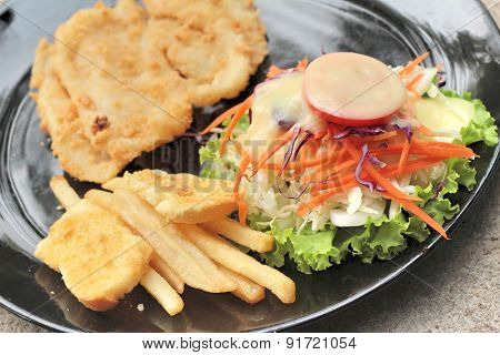 Fish Steaks And Vegetable Salad With French Fries.