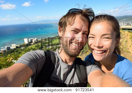 Selfie couple travel fun - Tourists on Hawaii taking selfie photo of Honolulu and Waikiki beach. Woman and man on hike visiting viewpoint lookout in Diamond Head State Monument and park, Oahu, USA.