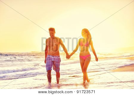 Happy couple on beach vacations holding hands in love. Holidays in sunset, young healthy adults together relaxing walking on summer day. Asian mixed race woman, Caucasian man.