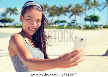Selfie taking young fitness happy woman on palm beach with smartphone after workout. Healthy lifestyle with multicultural Asian Caucasian female model in 20s.