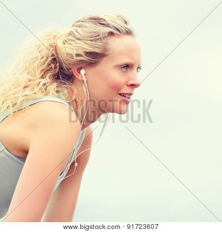 Active young fit woman exercising with earphones. Young fitness woman taking a break outside in summer fitness workout. Beautiful caucasian female model in running lifestyle listening to music.