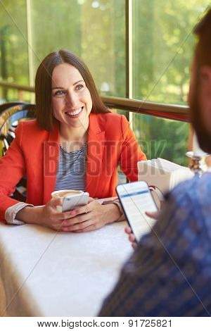man and woman with smartphones sitting on cafe. smiley woman looking at man