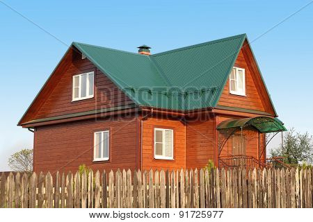 Wooden House Under Green Metal Roof With White Plastic Windows With Jalousie