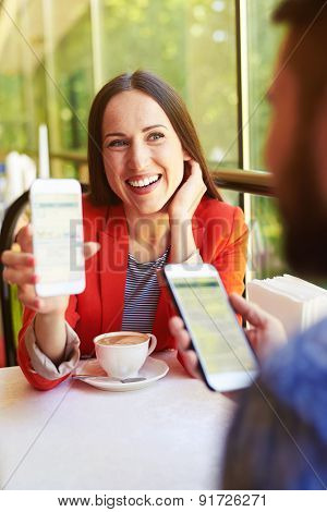 laughing young woman showing her mobilephone to man at cafe