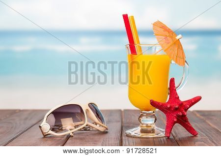 Juice and sunglasses on a wooden table