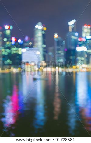 City blur bokeh lights during twilight with water reflection