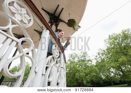 Low angle view of young woman using cell phone on porch