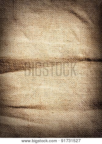 Old dirty brown burlap texture. Vertical woven fabric