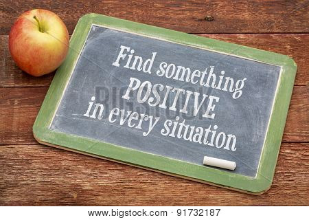 Find something positive in every situation  - motivational  words on a slate blackboard against red barn wood