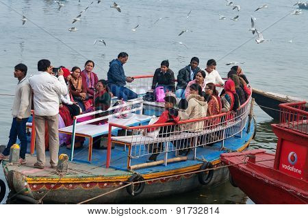 Indian Tourists Are Surrounded By Seagulls On Boat On The River Ganges. Varanasi