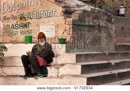 Indian Man Sits On Steps In Manmandir Ghat Near Sacred River Ganges In Varanasi