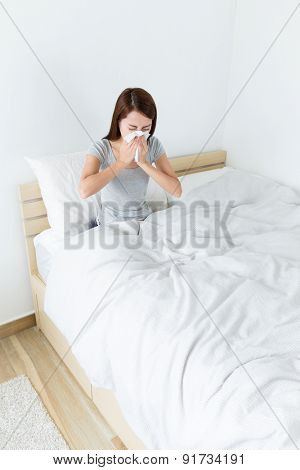 Asian woman feeling sick and sneeze at living room