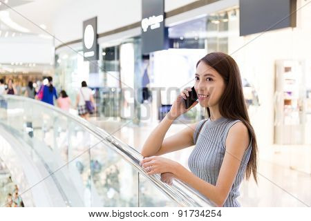 Woman talk to cellphone at shopping mall