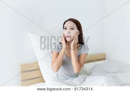 Young woman using the facial mask on bed