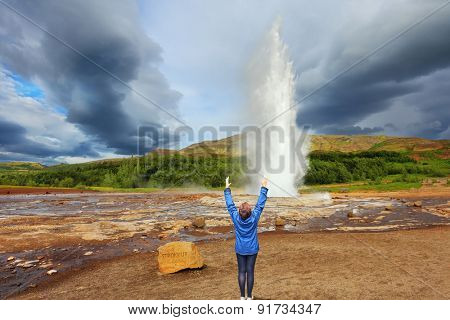 Woman -turist delighted geyser Strokkur. High column of hot water and steam . Gushing geyser Strokkur.