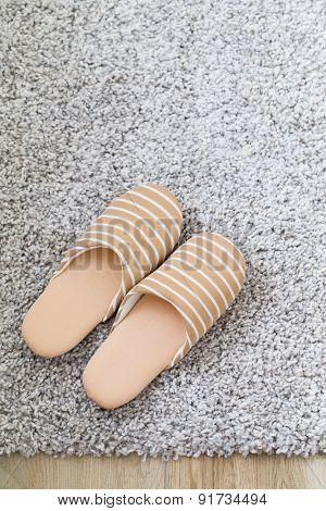 Brown slippers on grey carpet