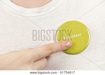 Closeup on female hand pointing to green volunteer button