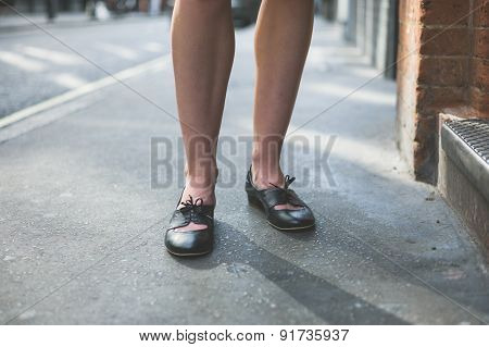Legs Of Woman Standing On The Pavement