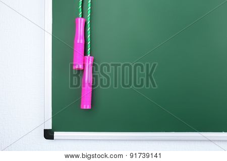 Skipping rope on green blackboard background