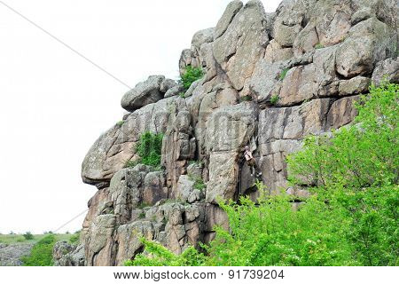 Man climbing on rock over sky background