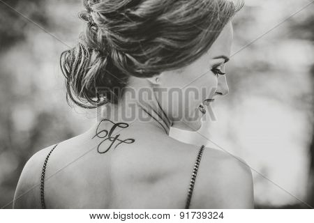 Portrait Of Young Girl With Tattoo On The Neck