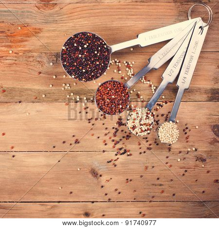 Mix of quinoa grain in metal measuring spoons