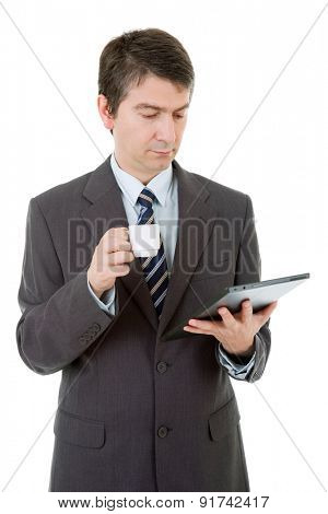 Portrait of a businessman looking at tablet pc and holding cup of coffee, isolated