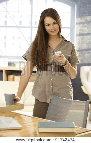 Young woman using mobilephone, standing at table.