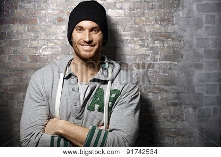 Portrait of happy young casual man standing over brick wall