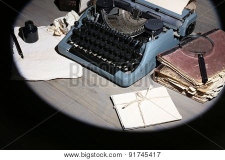 Retro typewriter in lamplight on wooden background