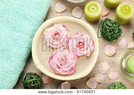 Bowl of spa water with flowers on wooden table, closeup